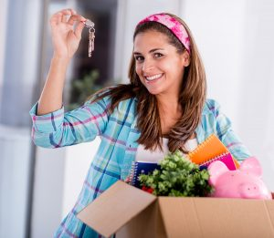 Young woman with keys to her new apartment holding a box of personal effects
